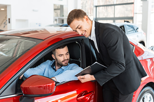 Dealer showing man about new car